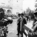 Vľavo filmová kamera, po ulici kráčajú: vľavo herec Jan Tříska a vpravo herec Ivan Mistrík, vpravo stojí režisér Jozef Režucha
