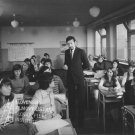 V strede v školskej triede stojí s perom v ruke Ivan Krivosudský (Cosínus), žiaci v laviciach