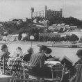 Ľudia sedia pri stoloch na nábreží pri Dunaji v Bratislave, v pozadí vidno bratislavský hrad a okolie