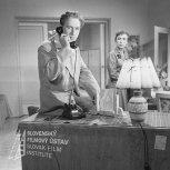 Negatív fotografie z filmu Previerka lásky (1956). Vľavo sedí na stole a telefonuje Elo Romančík (Juraj Horárik), vpravo stojí Hana Hegerová (Ľudmila Petušková)