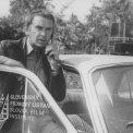 V otvorených dverách auta stojí a telefonuje Svatopluk Matyáš (major Vanek)