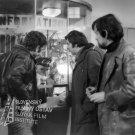 Vpravo stojí Vladimír Slosjar (grécky robotník v Zumbachovej firme), v strede stojí Vladimír Bartoň (Georgis Revidis, grécky robotník v Zumbachovej firme) a vpravo stojí s cigaretou v ústach František Velecký (grécky robotník v Zumbachovej firme), všetci traja stoja v metre pri okienku Information