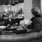 Pri stole s jedlom sedia: Božidara Turzonovová (Katarína Hornová, Mikeschova sekretárka) a Ľubo Roman (novinár Gabriel Hýbl)