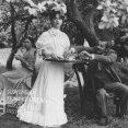 V záhrade pod stromami: vľavo sedí so šálkou čaju v rukách Mária Mačáková (Pauluša), v strede stojí s táckou v rukách Erika Ozsda (Božena Slančíková), ostatní