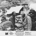 Horolezci sa vítajú pri stretnutí v tábore, v strede si dvaja podávajú ruky, obidvaja sú zarastení, okolo nich stoja ešte dvaja muži, za nimi vidno dva stany, kamene, trávu a mierne zasneženú pôdu