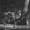 Fotografia z filmu Štyridsaťštyri (1957). V lese pri strome čupia v uniformách a so zbraňami v rukách: vľavo Dušan Blaškovič (vojak Tóno Mikleš) a vpravo Juraj Sarvaš (vojak Viktor Kolibec)