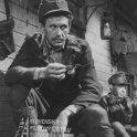 Fotografia z filmu Štyridsaťštyri (1957). V popredí sedí s cigaretou v ruke a v uniforme Július Vašek (kaprál Matej Frujak), v pozadí sedí v uniforme Vladimír Kostovič (vojak)