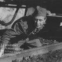 Na koľajniciach pod vlakom kľačí v uniforme Karol Machata (Ján Soviar)